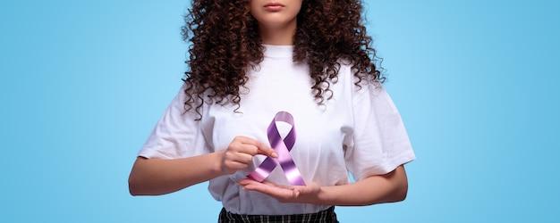 Weltkrebstag. frau, die lila band symbol des kampfkrebstages hält. isolierter blauer hintergrund