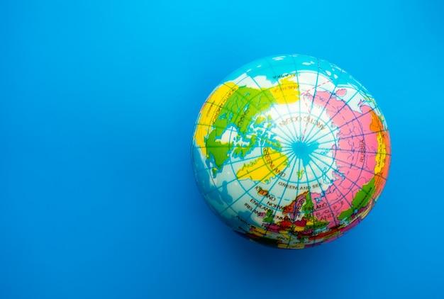 Weltkugelball auf hintergrund des blauen papiers