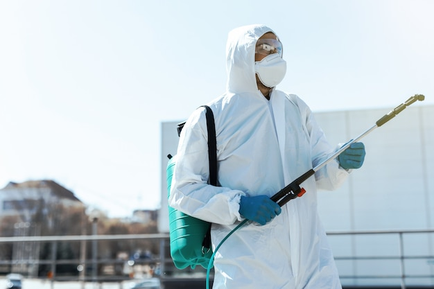 Weltpandemie. desinfektionsgerät in schutzanzug und maske, das desinfektionschemikalien im freien aufbewahrt