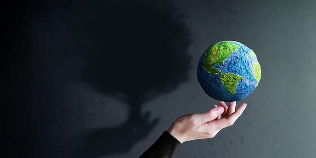 Welttag der erde, esg-konzept. grüne energie, erneuerbare und nachhaltige ressourcen. umwelt- und ökologiepflege. handgeste, die einen grünen handgemachten globus schweben lässt. big tree shadow beschattung an der wand