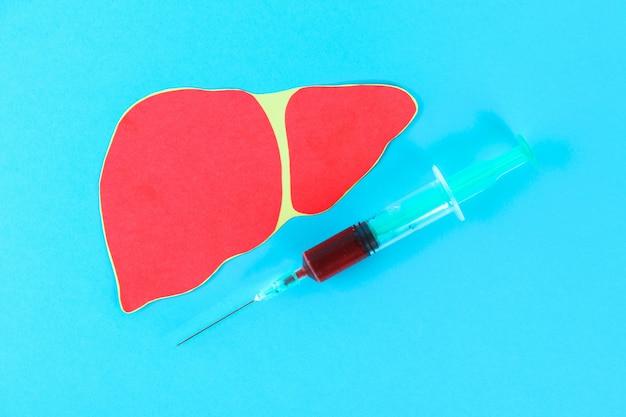 Welttag der hepatitis. 28. juni eine spritze mit blut und einer leber auf einer blauen tabelle