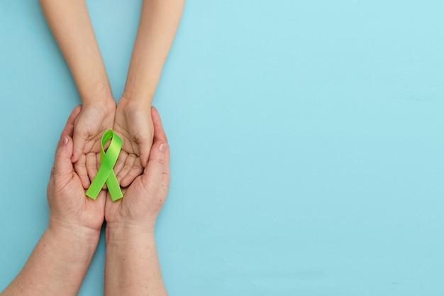 Welttag des bewusstseins für psychische gesundheiterwachsene und kinderhände, die grünes band auf blauem hintergrund halten