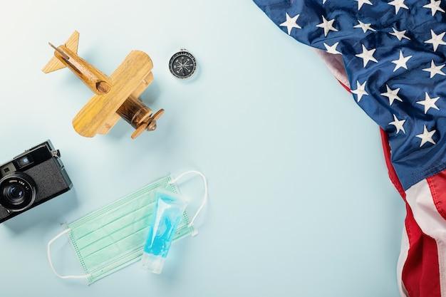 Welttourismustag während der coronavirus-pandemie-modellflugzeug mit gesichtsmaske und amerikanischer flagge