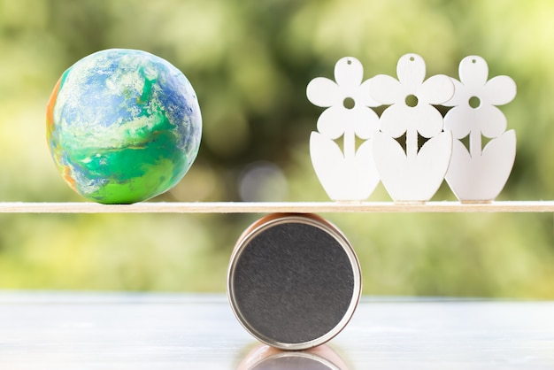 Weltumwelttagkonzept: globales modell mit hölzernem baum auf hölzerner runder kastenbalance