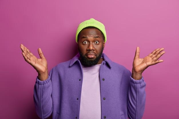 Wen interessiert das? zögernder schwarzer bärtiger mann spreizt palmen mit fragendem blick, sieht keinen ausweg in schwieriger situation, gekleidet in modisches outfit, drückt unsicherheit aus