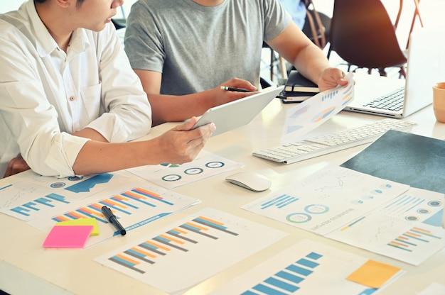 Wenden sie sich an junge geschäftsmannsitzung des startunternehmens auf schreibtisch.