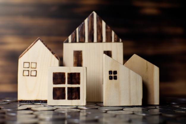 Wenig holzhausmodell mit münzen auf der planke, geld für wohnkonzept sparend.