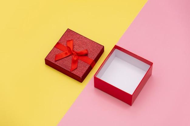 Wenig offene geschenkbox auf den rosa und gelben hintergründen.