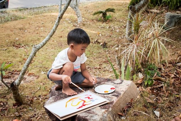 Wenig, panit spielend auf weißbuch im park