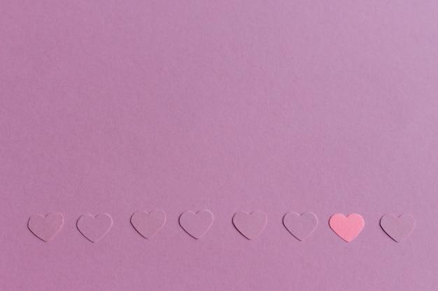 Wenig papierherzkonfettis auf rosa purpurrotem hintergrund