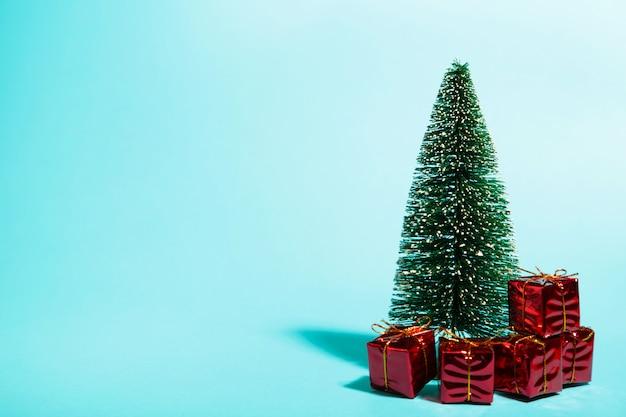 Wenig weihnachtsbaum mit geschenken auf blau mit kopienraum