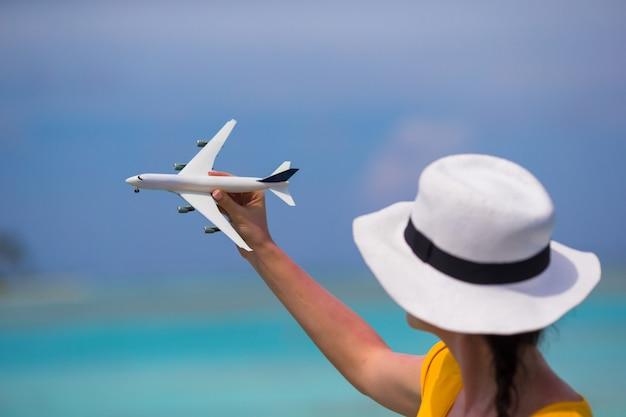 Wenig weißes spielzeugflugzeug auf hintergrund von türkismeer