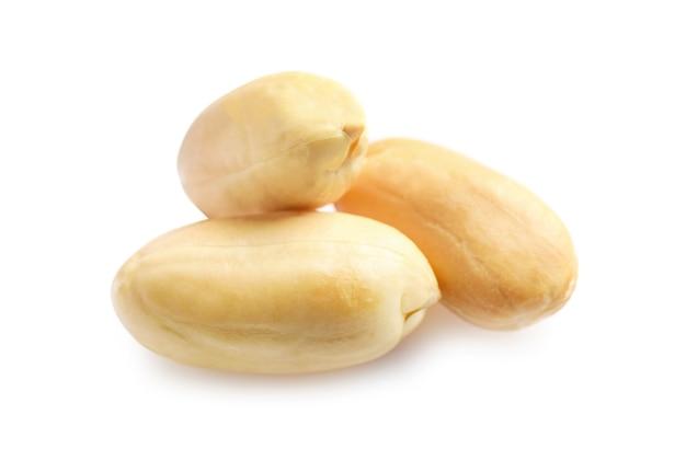 Wenige geschälte erdnüsse isoliert auf weiß