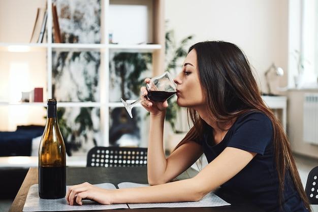 Wenn der wein in seltsame dinge kommt, kommt eine junge frau heraus, die allein rotwein trinkt