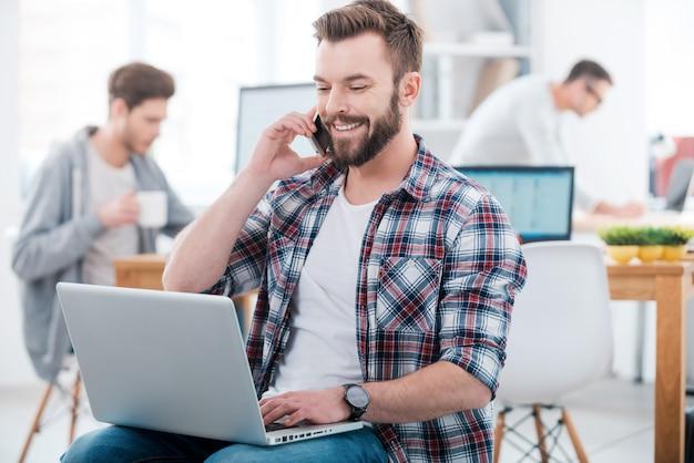 Wenn die arbeit in vollem gange ist. glücklicher junger mann, der am laptop arbeitet und am handy spricht, während zwei leute im hintergrund arbeiten