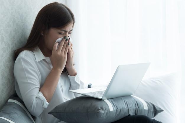 Wenn eine frau fieber hat, niest sie, während sie einen laptop im schlafzimmer benutzt.