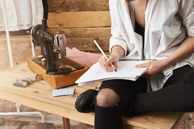 Wenn hobby echte arbeit wird. beschnittene aufnahme der kreativen designerin der kleidung, die auf tisch in der nähe der nähmaschine in ihrer werkstatt sitzt, notizen macht oder neues design für ihre kleidungslinie plant