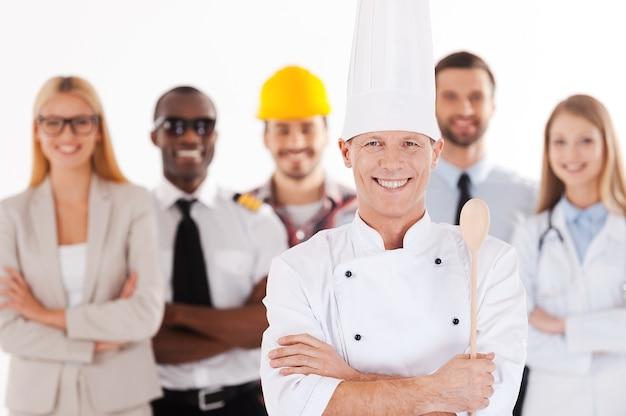 Wenn ich groß bin, werde ich koch. selbstbewusster männlicher koch in uniform, der die arme verschränkt hält und lächelt, während eine gruppe von menschen in verschiedenen berufen im hintergrund steht