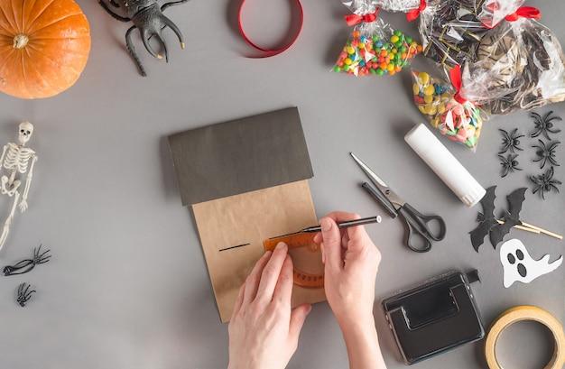 Wenn sie ein geschenk für halloween schritt für schritt mit einem lineal einpacken, markieren sie das zweite fenster des hauses mit einem filzstift