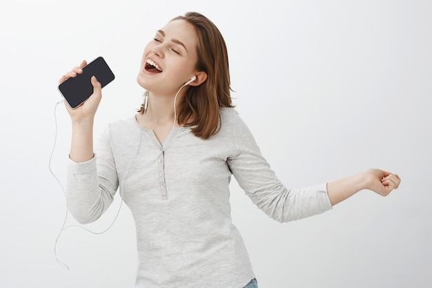 Wer braucht karaoke, wenn es ein smartphone gibt? glückliches charmantes junges mädchen mit kurzen braunen haaren, die wie stern aussehen, der entlang lieblingslied singt, das musik in den kopfhörern hört, die handy wie mikrofon halten