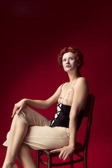 Wer hat die kontrolle. mittelalterliche rothaarige junge frau als herzogin im schwarzen korsett und in der nachtkleidung, die auf dem stuhl auf roter wand sitzt. konzept des vergleichs von epochen, moderne und renaissance.