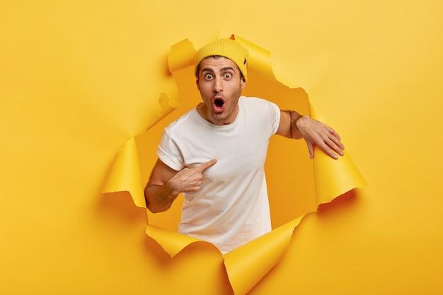 Wer, ich? der verblüffte emotionale mann zeigt auf sich selbst, gekleidet in ein lässiges weißes t-shirt