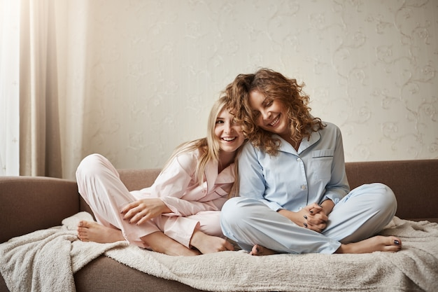 Wer kann besser verstehen als mutter. zwei schöne mädchen sitzen auf dem sofa in nachtwäsche, kuscheln, drücken zärtliche gefühle und zuneigung aus, sind enge freunde, klatschen und reden beiläufig