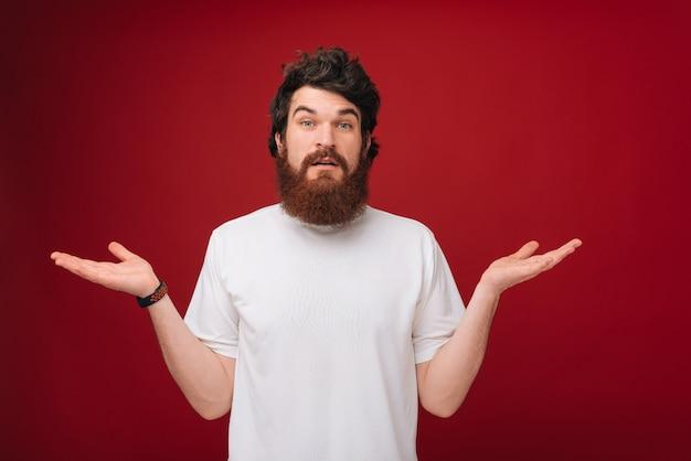 Wer weiß. ich bin es nicht. porträt eines verwirrten gutaussehenden mannes, der geste auf roter wand nicht kennt