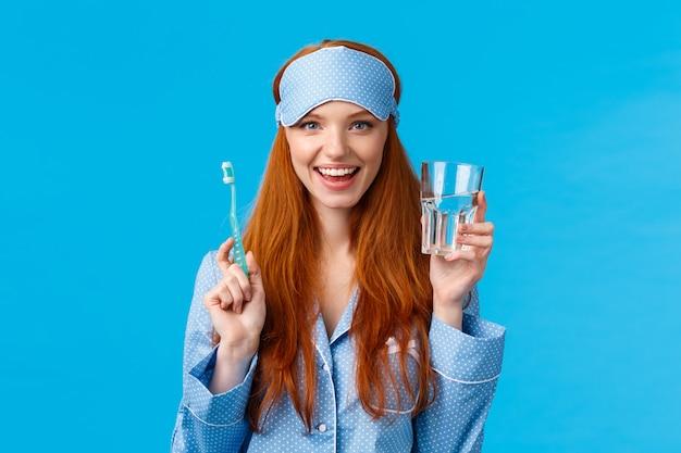 Werbe-, hygiene- und personenkonzept. feminine süße rothaarige mädchen fühlen sich optimistisch und enthusiastisch start tag richtig, trinkwasser, glas und zahnbürste halten, nachtwäsche und schlafmaske tragen