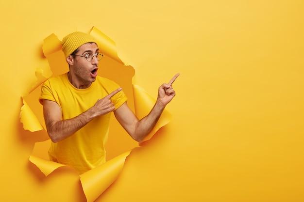 Werbebanner mit kopierplatz. emotional überraschter stilvoller mann trägt gelben hut