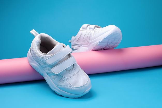 Werbebild eines gleichgewichts von zwei weißen mädchenlaufschuhen auf einer rosa langen papierröhre auf einem blauen...