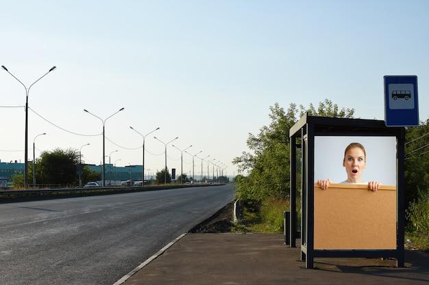 Werbelayout an einer bushaltestelleüberraschte junge frau mit einem schwarzen brett