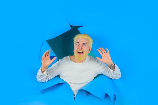 Werbemann macht loch in papier emotionen glücklicher bärtiger mann, der aus zerrissenem papierloch späht