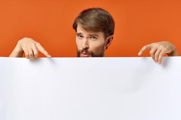 Werbeplakat in den händen eines mannes auf einer orange gestikulierten hand mit seinen händen copy space