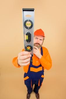 Werbung handwerker bärtiger baumeister bärtiger mann mit wasserwaage reparaturarbeiter in wasserwaage