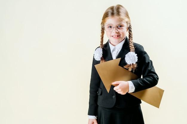 Werbung und kinderkonzept - lächelndes kleines mädchen in der schuluniform mit leerem pfeil nach links zeigend