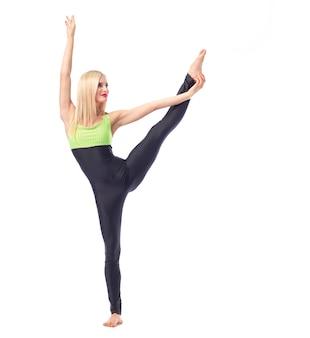 Werde gesund. schöne weibliche turnerin, die beindehnungsübung macht, isolierte gymnastikgymnastik-aktivität sportliches konzept