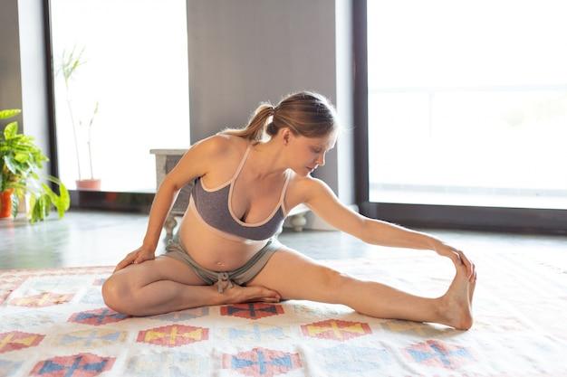 Werdende mutter, die zu hause yoga macht