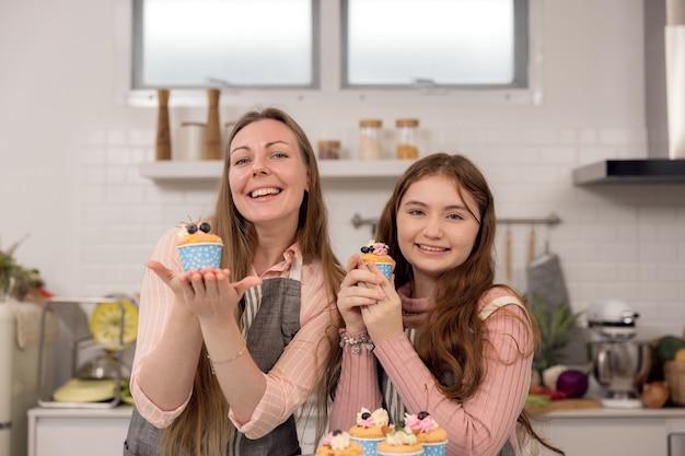 Werdende mutter und tochter dekorieren cupcakes auf einem küchentisch, haben eine gute zeit zusammen beim essen von frisch gebackenem gebäck