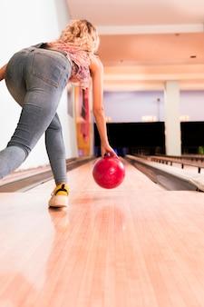 Werfende bowlingkugel der frau der niedrigen ansicht