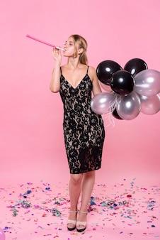 Werfende konfettis der frau und halten von ballonen