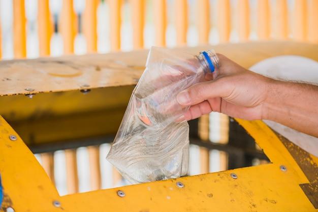 Werfende plastikflasche des mannes im papierkorb