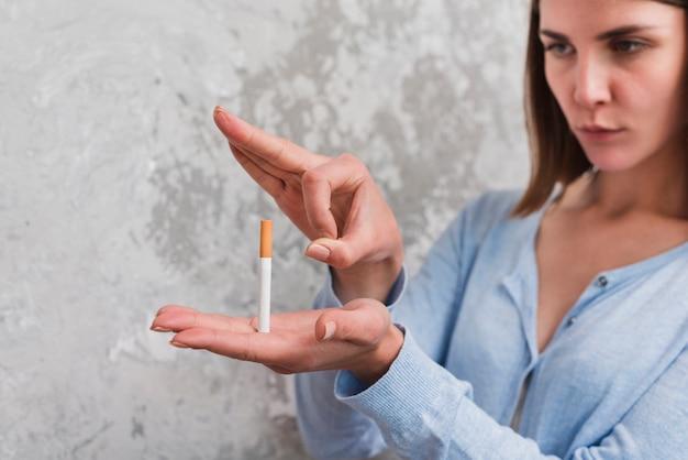Werfende zigarette der frau durch ihren finger gegen verwitterte wand