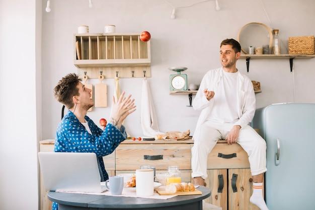 Werfender apfel des glücklichen mannes in richtung zu seinem freund, der vor tabelle mit lebensmittel sitzt