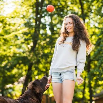Werfender ball der jungen frau für ihren hund am park