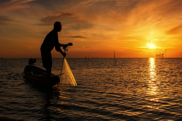 Werfendes fischernetz während des sonnenaufgangs, thailand
