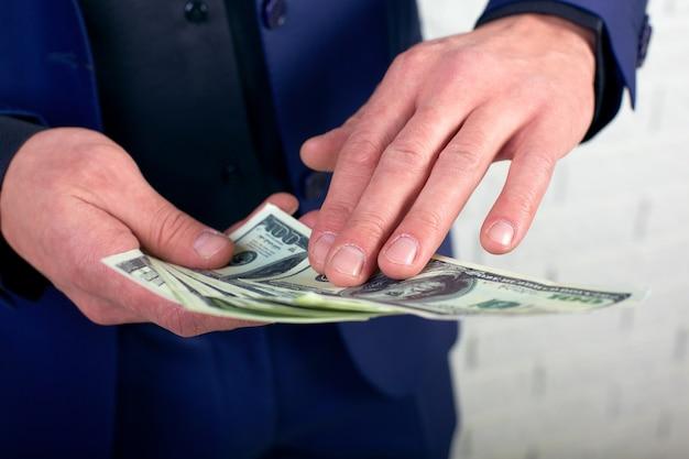 Werfendes geld des geschäftsmannes auf weißem hintergrund. mann in anzug tragen geldverschwendung, werfen banknoten, dollar.