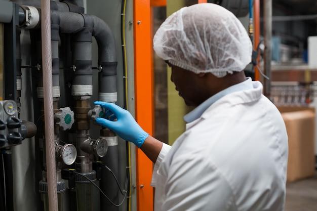 Werksingenieur überwacht ein manometer im werk