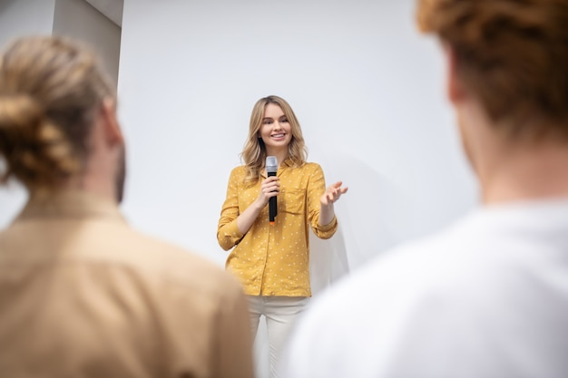 Werkstatt. blonde trainerin mit mikrofon im gespräch mit dem publikum