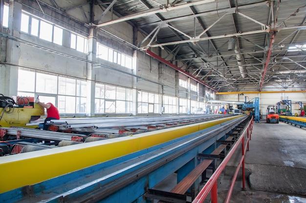 Werkstatt zur herstellung von aluminiumprofilen. förderband mit aluminiumprofilen